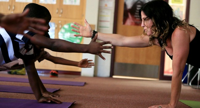 Social worker and students reach toward one another in a yoga pose.