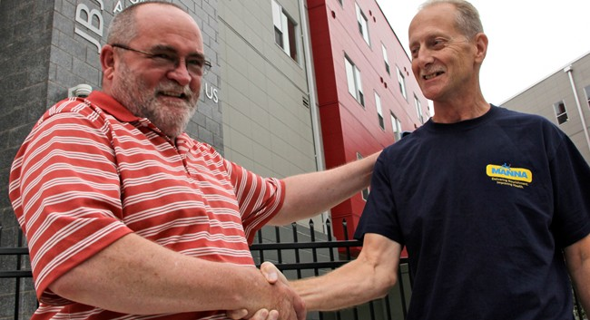 Two military veterans shake hands in from of the new housing complex built by rocker Bon Jovi.