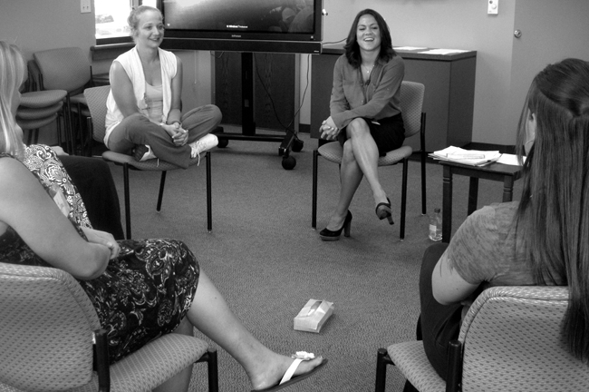 Group of women sit in a circle, box of tissues in the middle