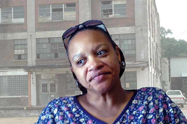 Portrait of Shelia Barnett against the backdrop of a decrepit factory.